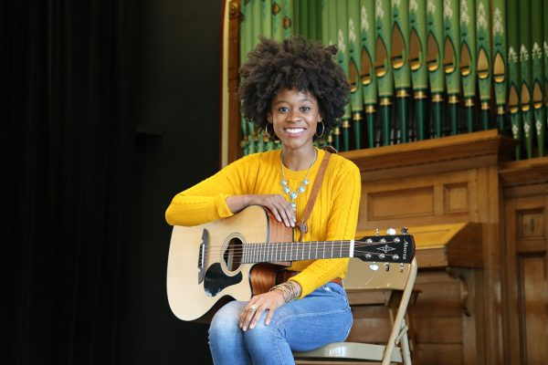 Woman in yellow sweater sitting with a guitar