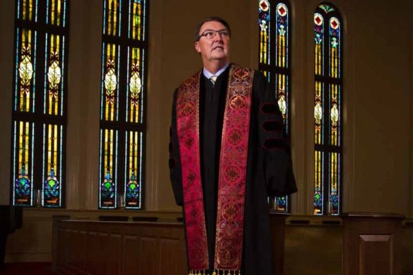 Dr. Conner stands in a church